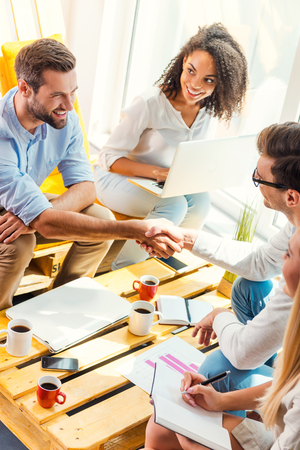 Photo for Welcome on board! Two cheerful young men sitting at the wooden desk in office and shaking hands while two beautiful women looking at them and smiling - Royalty Free Image