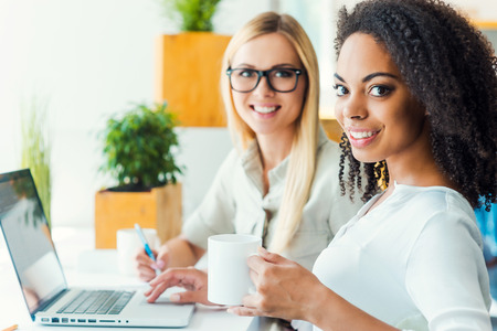 Foto de Two minds are better than one. Two smiling young women looking at camera and smiling while sitting at working place - Imagen libre de derechos