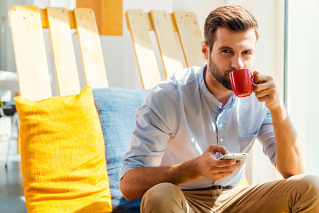 Photo pour Inspired with cup of fresh coffee. Handsome young man holding mobile phone and drinking coffee while sitting in the rest area of the office - image libre de droit