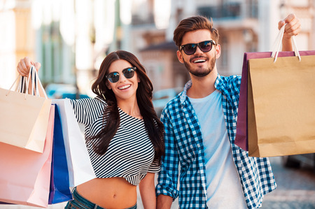 Photo for They love shopping together. Cheerful young loving couple stretching out shopping bags and smiling while walking along the street - Royalty Free Image