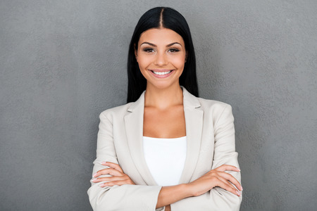 Foto de Charming businesswoman. Smiling young businesswoman keeping arms crossed and looking at camera while standing against grey background - Imagen libre de derechos