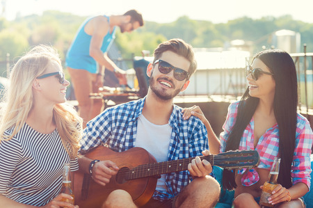 Photo for Sharing good time. Three cheerful young people bonding to each other and sitting on the bean bag with guitar while man barbecuing in the background - Royalty Free Image