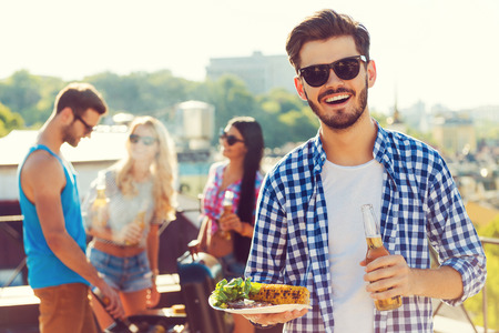 Photo for Good food with best friends. Smiling young man holding bottle with beer and plate with food while three people barbecuing in the background - Royalty Free Image