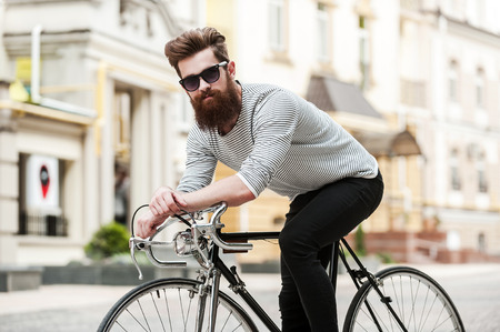 Foto de Time to hit the road. Handsome young bearded man looking at camera while sitting on his bicycle outdoors - Imagen libre de derechos