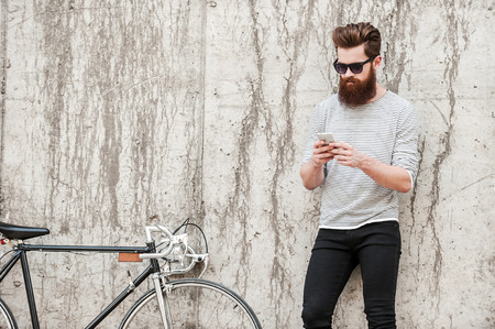 Foto de Chilling after good ride. Handsome young bearded man holding mobile phone while standing near his bicycle against the concrete wall - Imagen libre de derechos