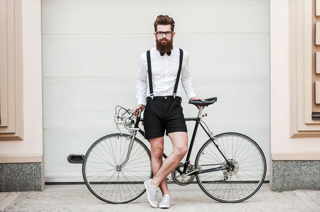Foto de Are you ready for ride? Full length of handsome young bearded man leaning at his bicycle and looking at camera while standing outdoors - Imagen libre de derechos