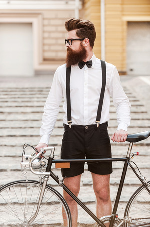 Foto de Man n style. Confident young bearded man holding hands on his bicycle and looking away while standing outdoors - Imagen libre de derechos