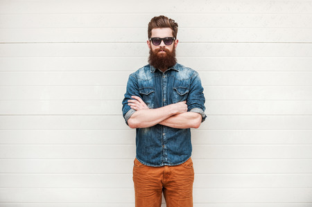 Photo pour Bearded and stylish. Confident young bearded man looking at camera and keeping arms crossed while standing outdoors - image libre de droit