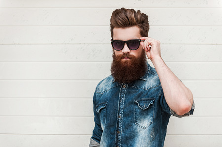 Foto de Rugged and manly. Confident young bearded man looking at camera and adjusting eyewear while standing outdoors - Imagen libre de derechos