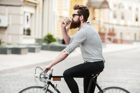 Foto de Coffee on the go. Side view of young bearded man drinking coffee while sitting on his bicycle outdoors - Imagen libre de derechos