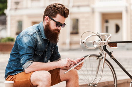Photo pour Catching up on some news. Handsome young bearded man holding digital tabletwhile sitting near his bicycle outdoors - image libre de droit