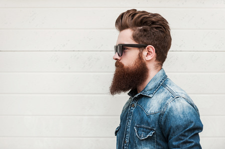 Foto de Perfect style. Side view of young bearded man in eyewear looking away while standing outdoors - Imagen libre de derechos