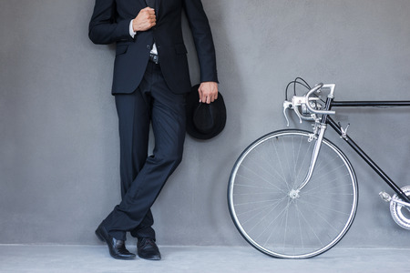 Foto de Elegant style. Close-up of young businessmanholding hat and adjusting his jacket while standing near his bicycle against grey background - Imagen libre de derechos