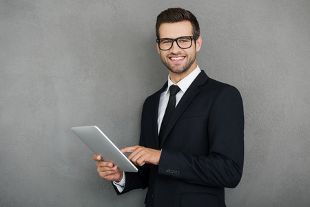 Photo pour Doing his business in easy way. Happy young businessman holding digital tablet and looking at camera while standing against grey background - image libre de droit