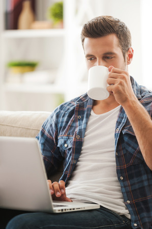 Foto de Getting the latest news online. Handsome young man working on laptop and drinking coffee while sitting on sofa - Imagen libre de derechos