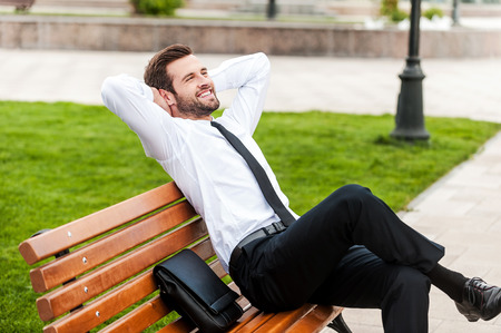 Foto de Enjoying green spaces in his city. Top view of happy young businessman keeping eyes closed and holding hands behind head while sitting on the bench outdoors - Imagen libre de derechos
