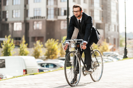 Foto de Cycling is the way to progress! Full length of handsome young businessman looking forward while riding on his bicycle - Imagen libre de derechos