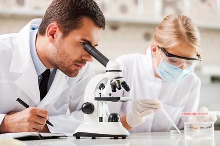 Foto de Improving modern medicine. Two young scientists making experiments while sitting in the laboratory - Imagen libre de derechos