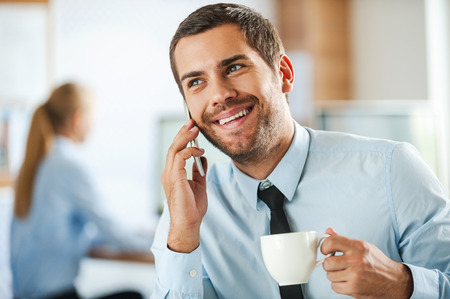 Photo for Always in good mood. Cheerful young businessman in formalwear talking on the mobile phone and holding cup of coffee while his female colleague working in the background - Royalty Free Image