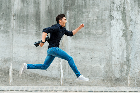 Foto per Hurrying to be first. Full length of young photographer running against a concrete wall - Immagine Royalty Free