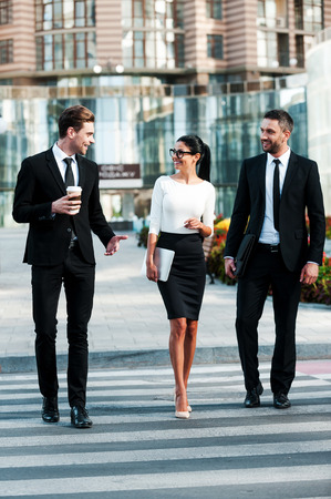 Photo for On the way to success. Full length of three smiling business people talking to each other while crossing the street - Royalty Free Image
