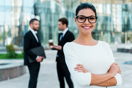 Foto de Confident businesswoman. Smiling young businesswoman keeping arms crossed and looking at camera while two her male colleagues talking to each other in the background - Imagen libre de derechos
