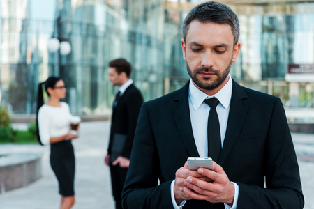 Photo for Business texting. Serious young businessman holding mobile phone and looking at it while two his colleagues talking to each other in the background - Royalty Free Image