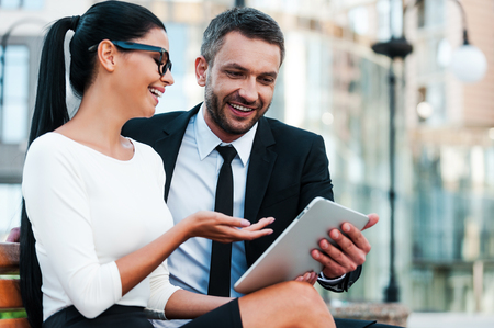 Foto de Keeping up with the latest news. Low angle view of cheerful young businesswoman pointing at digital tablet while her male colleague holding it - Imagen libre de derechos