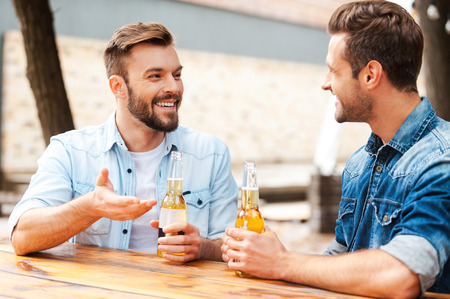 Foto de Good talk with friend. Two joyful young men talking to each other and holding bottles with beer while standing outdoors - Imagen libre de derechos