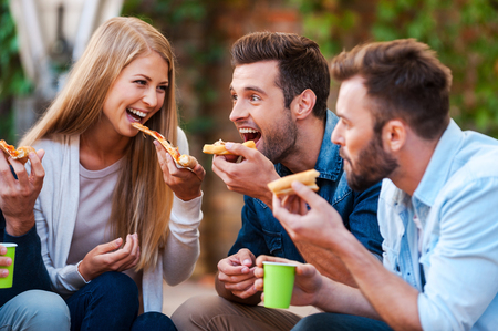 Foto de Pizza lovers. Group of playful young people eating pizza while having fun together - Imagen libre de derechos