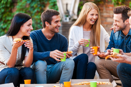 Photo pour Spending good time with friends. Group of cheerful young people talking to each other and eating pizza while sitting outdoors - image libre de droit