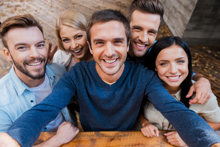 Photo pour Funny selfie with friends. Top view of five cheerful young people making selfie and smiling while standing outdoors - image libre de droit