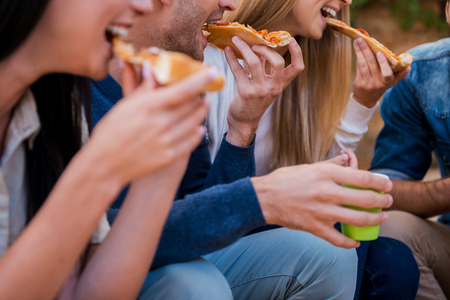 Photo pour Time for pizza! Group of young people eating pizza while sitting outdoors - image libre de droit