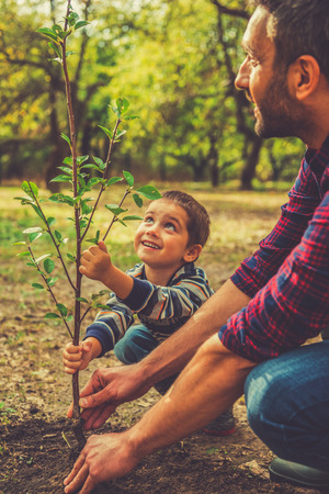Foto de Giving a new life. Cheerful little boy helping his father to plant the tree while working together in the garden - Imagen libre de derechos