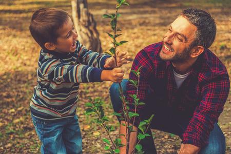 Foto de Planting a family tree. Happy young man planting a tree while his little son helping him - Imagen libre de derechos
