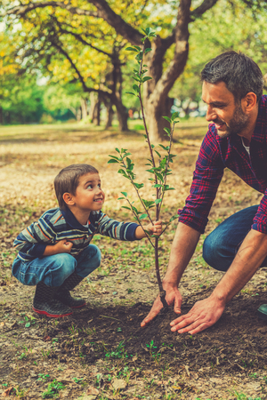 Foto de This tree will grow with you! Playful little boy helping his father to plant the tree while working together in the garden - Imagen libre de derechos