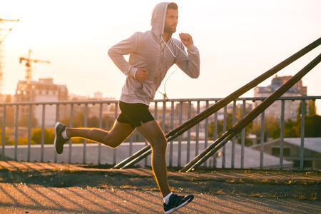 Foto de Moving to his goal. Side view of confident young man running along the bridge - Imagen libre de derechos
