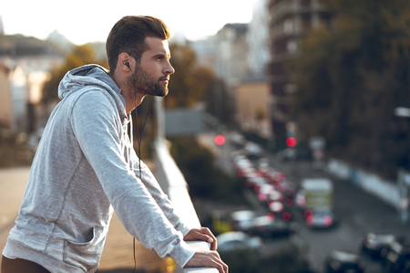 Photo for In love with his city. Side view of pensive young man in headphones looking away while standing on the bridge - Royalty Free Image