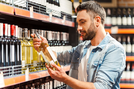 Foto de This should be fine. Side view of handsome young man holding bottle of wine and looking at it while standing in a wine store - Imagen libre de derechos