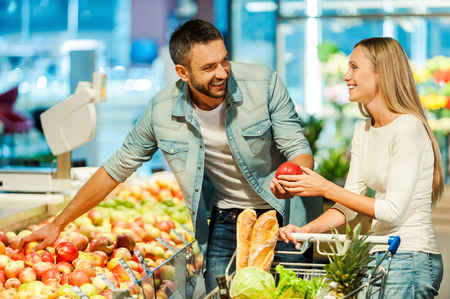 Photo for Beautiful young smiling couple choosing apples in supermarket together - Royalty Free Image