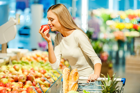 Foto de Beautiful young woman holding apple and smelling it with smile while standing in a food store - Imagen libre de derechos