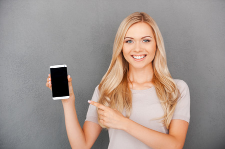 Photo for Copy space on her smart phone. Smiling young blond hair woman holding mobile phone and pointing at it while standing against grey background - Royalty Free Image