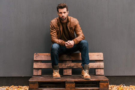 Foto de Confident and handsome. Handsome young man sitting on the wooden pallet and looking at camera with grey wall in the background and orange fallen leaves on the floor - Imagen libre de derechos