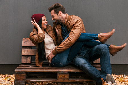 Photo for Playful couple. Playful young loving couple having fun together while sitting on the wooden pallet together with grey wall in the background and fallen leaves on ht floor - Royalty Free Image