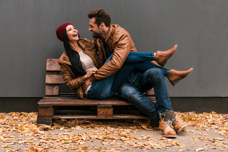 Foto de Carefree time together. Beautiful young couple having fun together while sitting on the wooden pallet together with grey wall in the background and fallen leaves on ht floor - Imagen libre de derechos