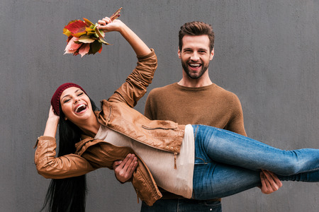 Photo for Love and fun. Beautiful young couple having fun together while standing against grey wall - Royalty Free Image