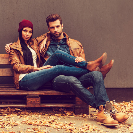 Photo pour Autumn style. Beautiful young couple bonding to each other while sitting on the wooden pallet with grey wall in the background and fallen leaves laying on the floor - image libre de droit
