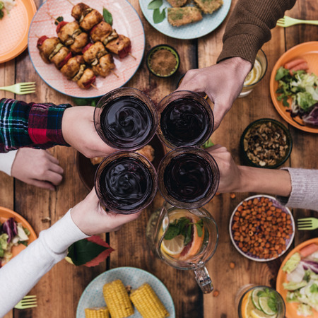 Foto de Cheers to friends! Top view of four people cheering with red wine while sitting at the rustic dining table - Imagen libre de derechos
