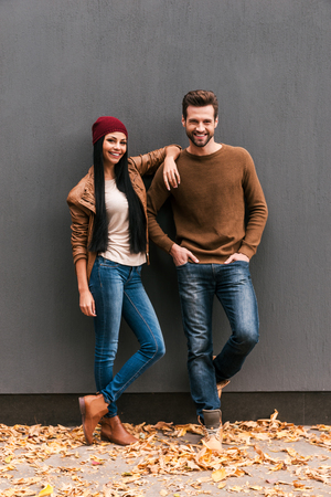 Photo for Young and free. Beautiful young couple bonding to each other and smiling while leaning at the grey wall with fallen leaves laying around them - Royalty Free Image