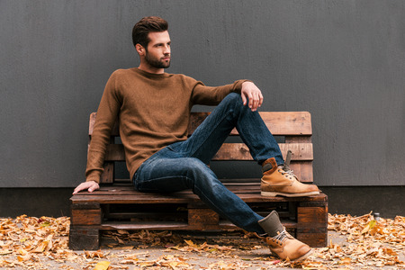 Foto de Casually handsome. Handsome young man sitting on the wooden pallet and looking away with grey wall in the background and orange fallen leaves on the floor - Imagen libre de derechos